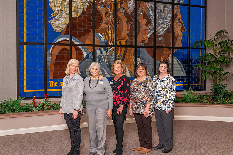 All the ladies at the Faces of Aging stained glass window on Life Care's corporate campus