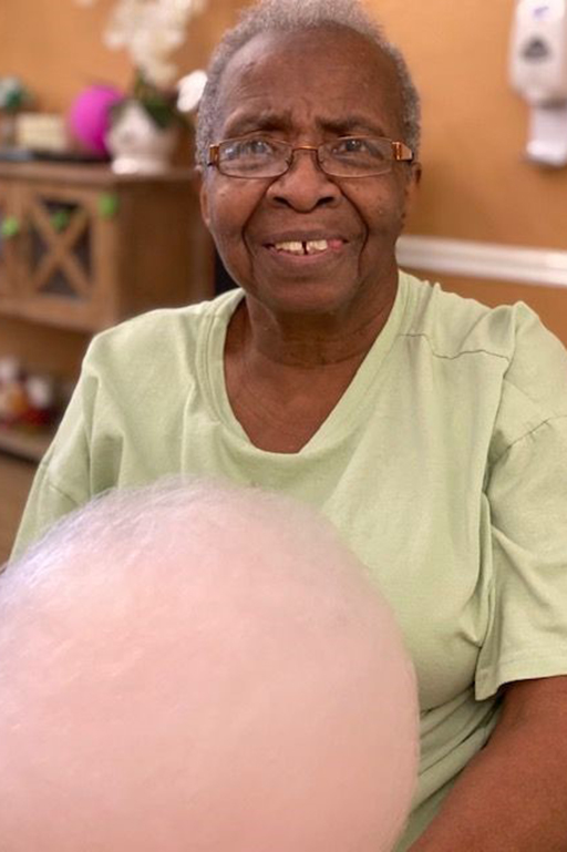 Ida Graham, a resident at Camellia Gardens of Life Care, enjoys cotton candy due to a community member's generous donation.
