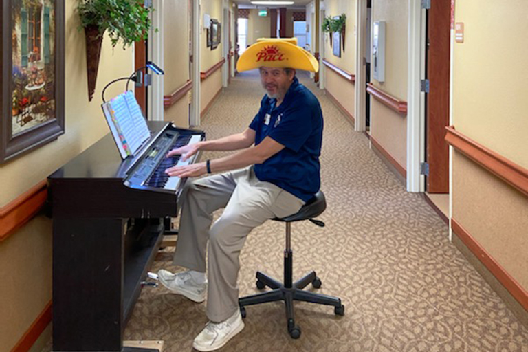 Kevin O?Neil, maintenance director, playing piano for residents at Villa Manor Care Center in Lakewood, Colorado