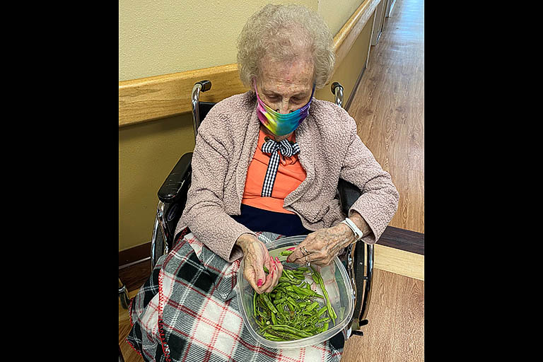 Residents have fun breaking beans at The Heritage Center